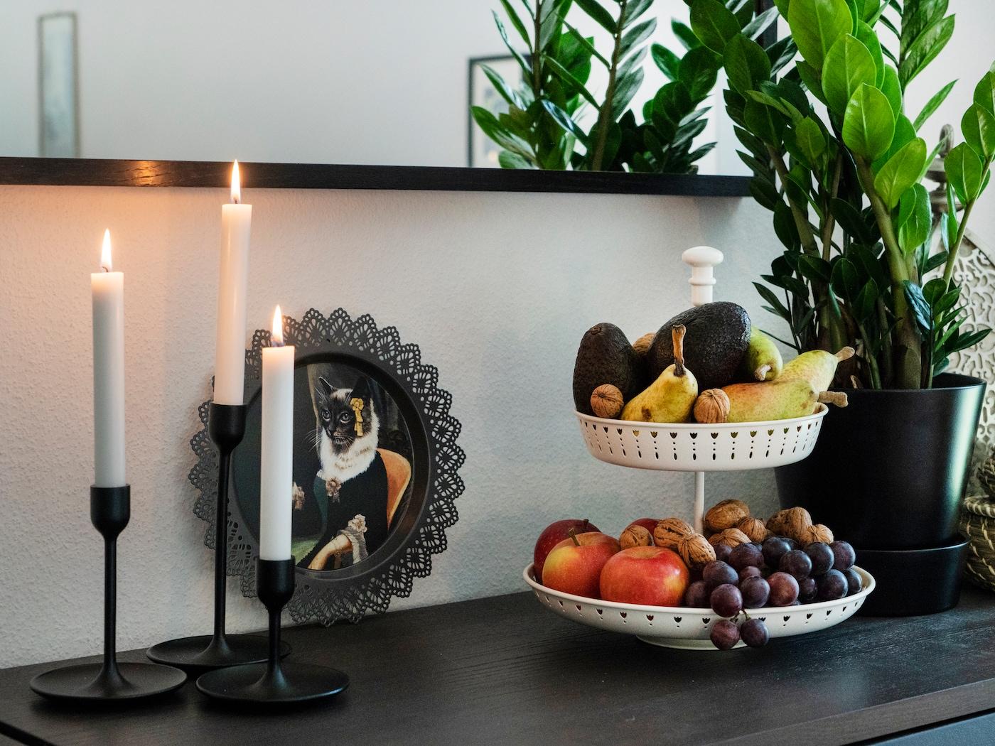 IKEA Kommode dekoriert mit IKEA Kerzenständer, IKEA Katzenbild, IKEA Pflanze und IKEA Etagere für Obst.