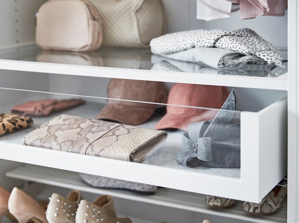 IKEA KOMPLEMENT storage drawers with glass fronts storing wallets, hats and accessories.