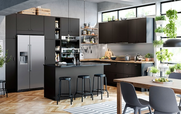 IKEA KUNGSBACKA recycled PET plastic black kitchen cabinet door fronts with black bar stools in an airy open plan kitchen.