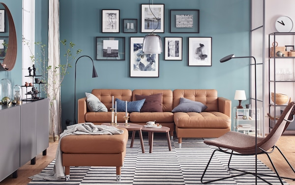 IKEA LANDSKRONA golden brown leather sofa with long chaise and footstool, against a teal wall in a living room space.
