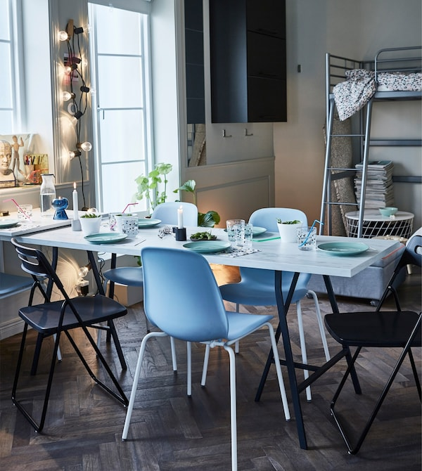 IKEA LEIFARNE scooped blue chairs surrounding a dining table.