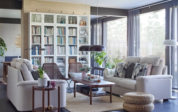 IKEA LIDHULT beige two-seater sofas and white BILLY glass bookcase shelves in a spacious living room setting.