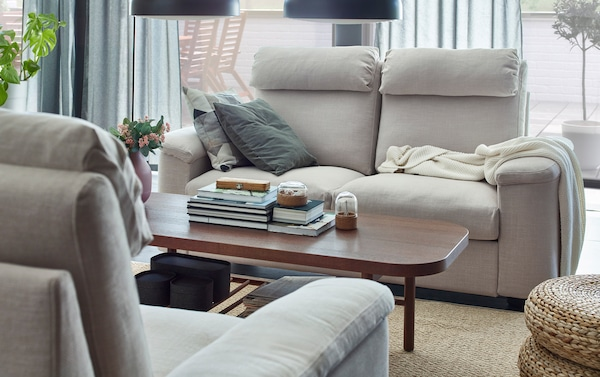 IKEA LIDHULT light beige sofas facing a dark brown coffee table.