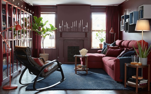 IKEA LIDHULT three-seater red and brown sofabed with long chaise in a red-walled living room.