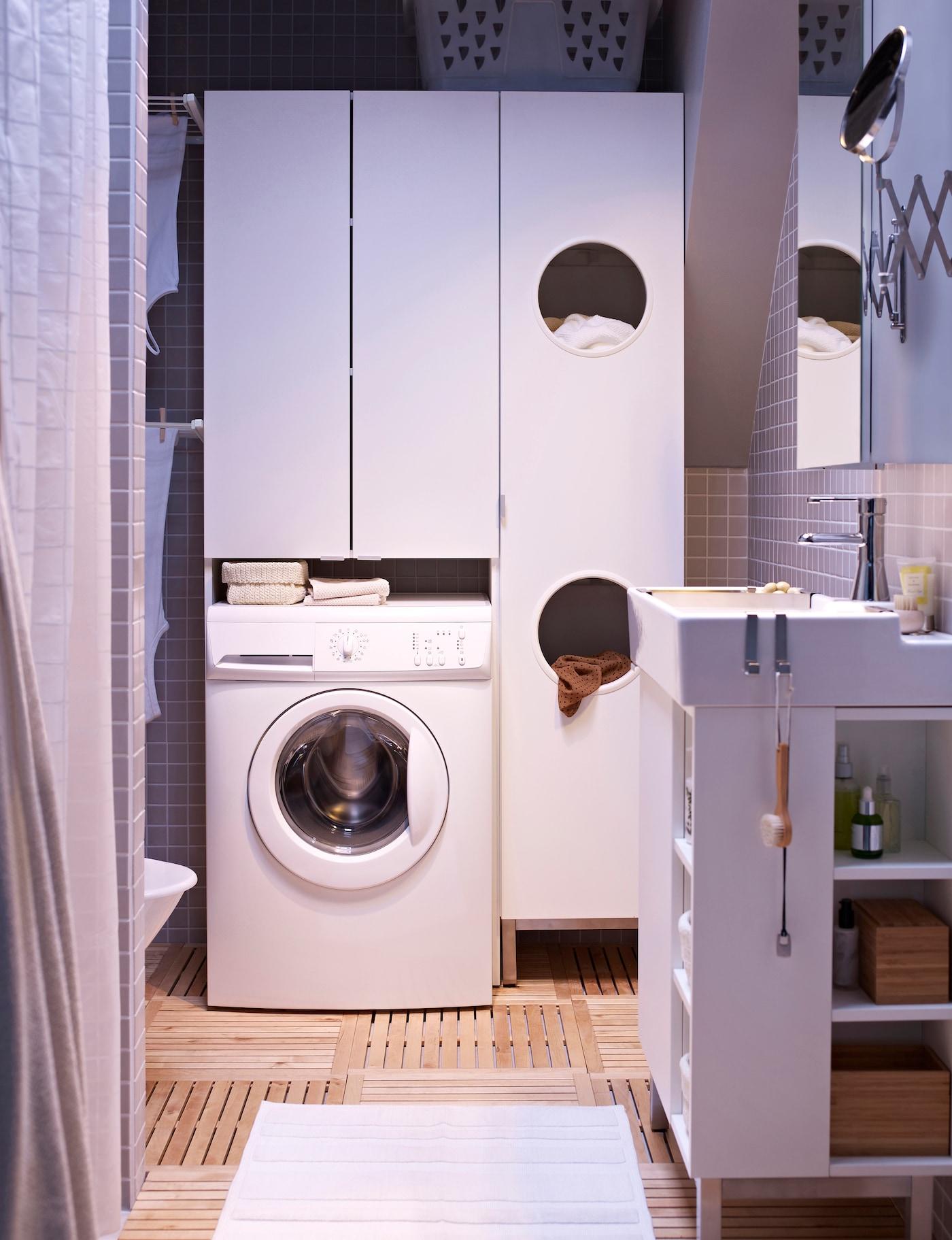 IKEA LILLÅNGEN smala tvättskåp i vitt i ett badrum med vit badrumsinredning. Under skåpet står en tvättmaskin placerad.