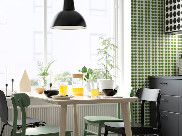 IKEA LISABO light ash veneer dining table, green RÖNNINGE chairs and SVENBERTIL black chairs in a dining room setting.