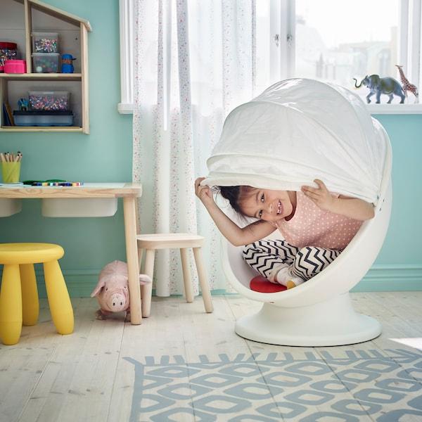 IKEA LÖMSK white swivel armchair with child sitting inside.