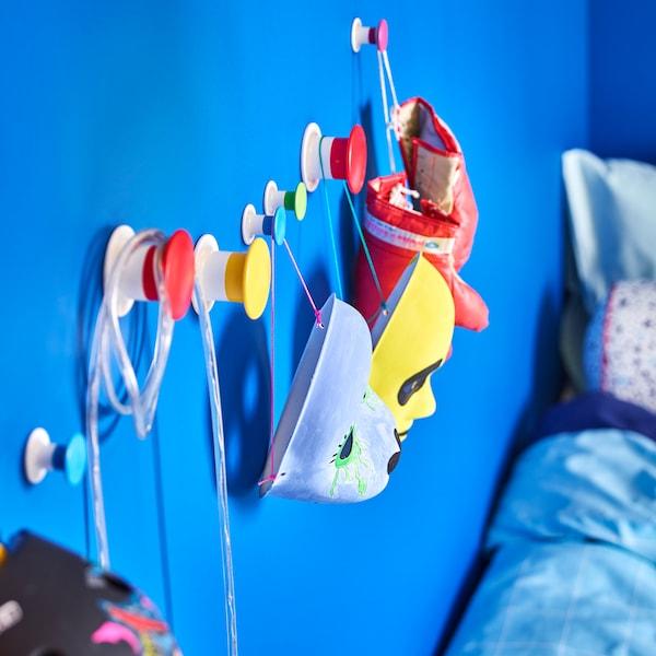 IKEA LUSTIGT colourful masks hung on LOSJÖN mounted hooks.