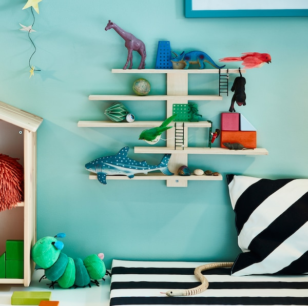 IKEA LUSTIGT light wooden pine display shelf mounted to the wall, holding toys and figurines.