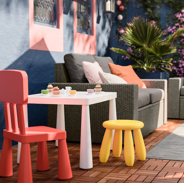 IKEA MAMMUT outdoor children's furniture including a low yellow stool, red chair and chunky white recycled plastic table.
