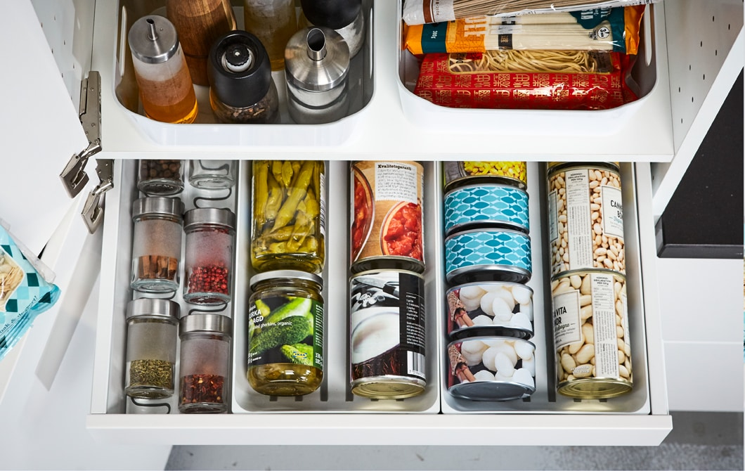 IKEA MAXIMERA white kitchen pantry drawer can keep your cans, tins, and spices organised, while VARIERA white plastic baskets hold oils, tall bottles and more.