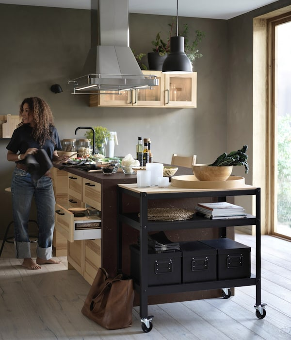 IKEA Metod kitchen with light wood fronts and a black-brown kitchen trolley.