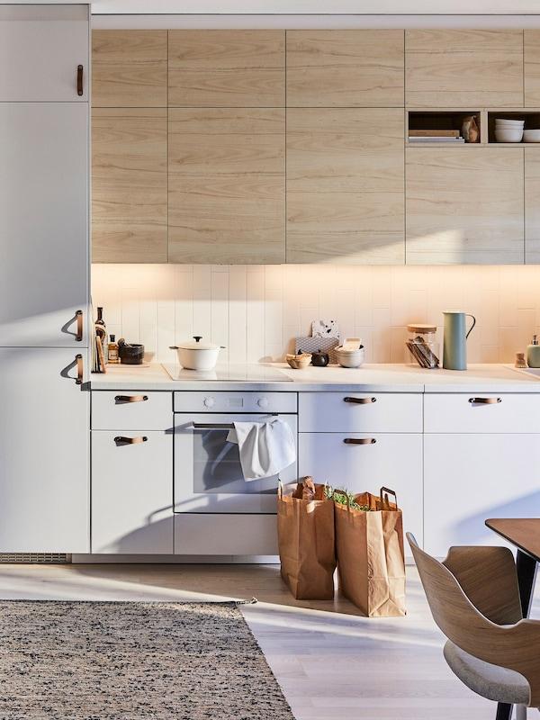 IKEA METOD konyha, világos fa ASKERSUND kőris hatású előlapokkal, MELHOLT síkszövött szőnyeggel.