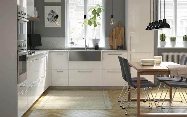 IKEA Metod Küche in Hochglanz weiss mit einer grossen Edelstahlspüle und Elektrogeräten. Davor steht ein Esstisch mit Stühlen.