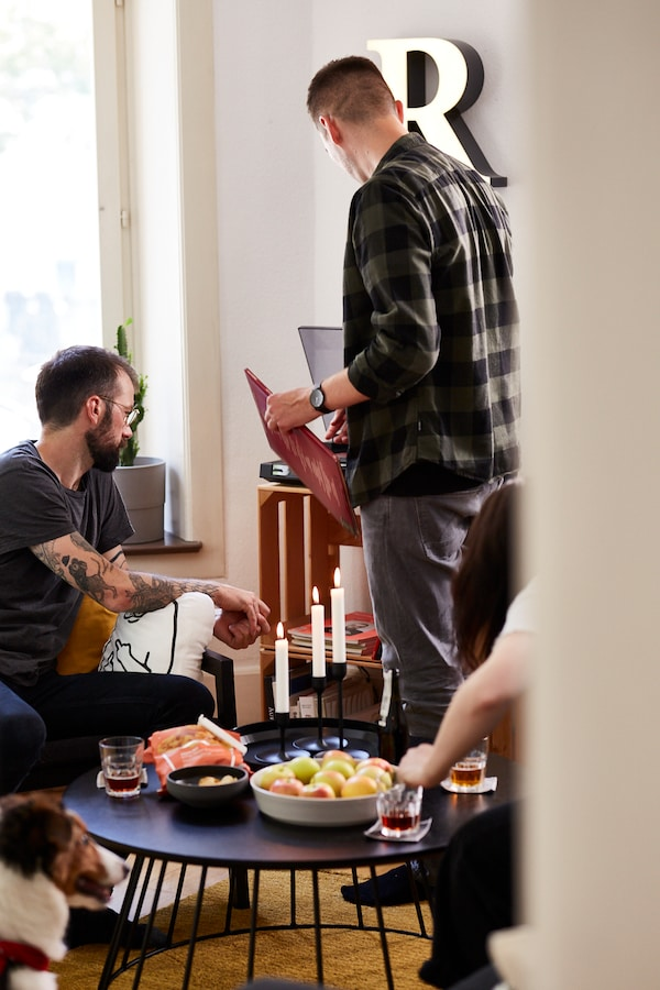 IKEA Mitarbeiter hört mit Freunden Musik und isst IKEA Chips.