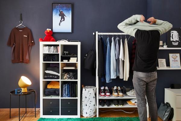 IKEA Mitarbeiter steht vor offenem IKEA Kleiderschrank.