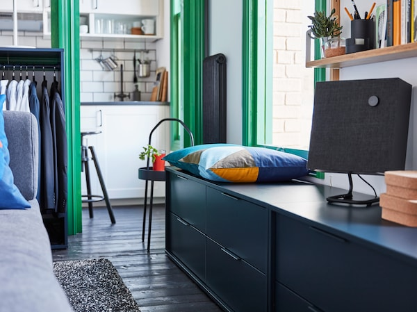 IKEA NORDMELA blue storage unit, being used as a bench with coloured cushion and ENEBY speaker.