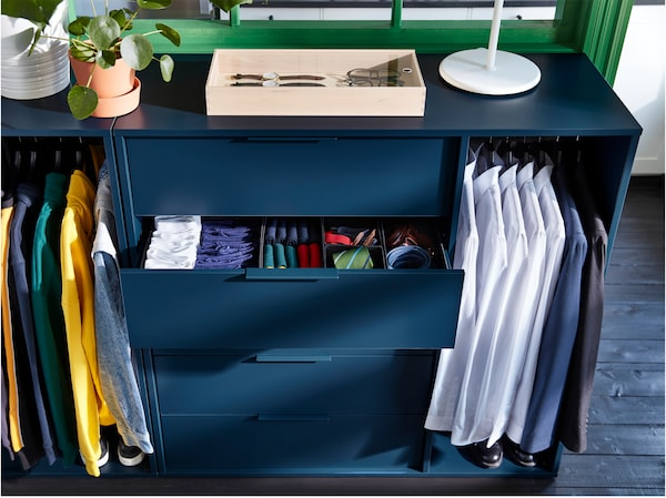 IKEA NORDMELA dark blue storage unit with one drawer open showing clothes.