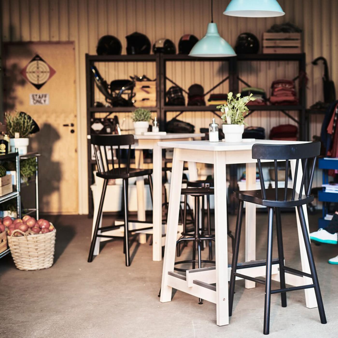 IKEA NORRÅKER light wood bar tables with high black bar chairs in a small farmhouse styled cafe setting.