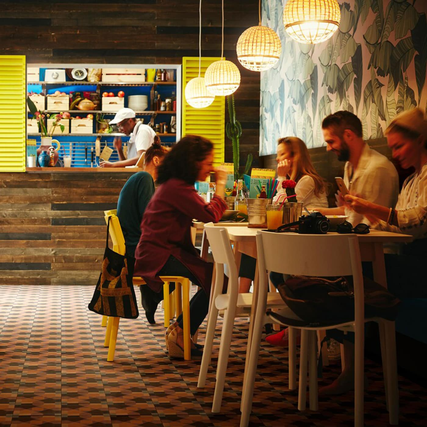 IKEA NORRÅKER white birch bar tables and birch bar stools in a colourful small restaurant setting with INDUSTRIELL bamboo woven pendant lamps.