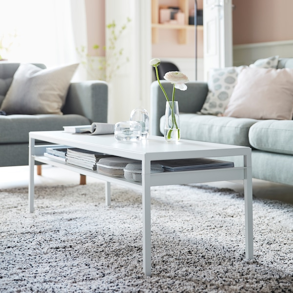 IKEA NYBODA long white coffee table with books stored underneath on a thin, slim shelf.