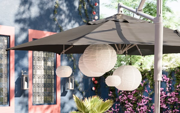 IKEA OXNÖ tiltable parasol frame and LINDÖJA black polyester canopy covering a collection of SOLVINDEN white paper lantern pendant lamps.