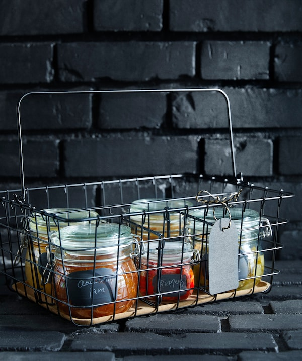 IKEA PLEJA wire basket filled with jars of homemade goodness.