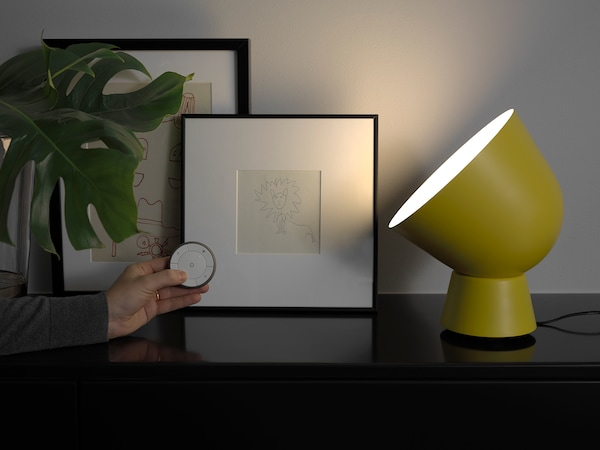 IKEA PS 2017 table lamp in front of two picture frames and a plant, with a hand holding a small circular watch-like object.