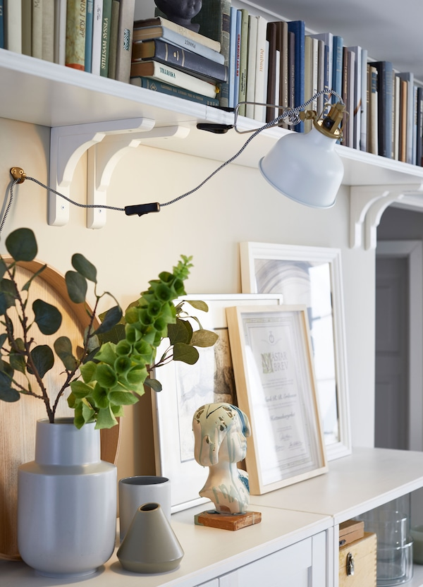IKEA RAMSHULT white brackets, with BERGSHULT white wall shelves mounted next to each other for an elongated storage solution.