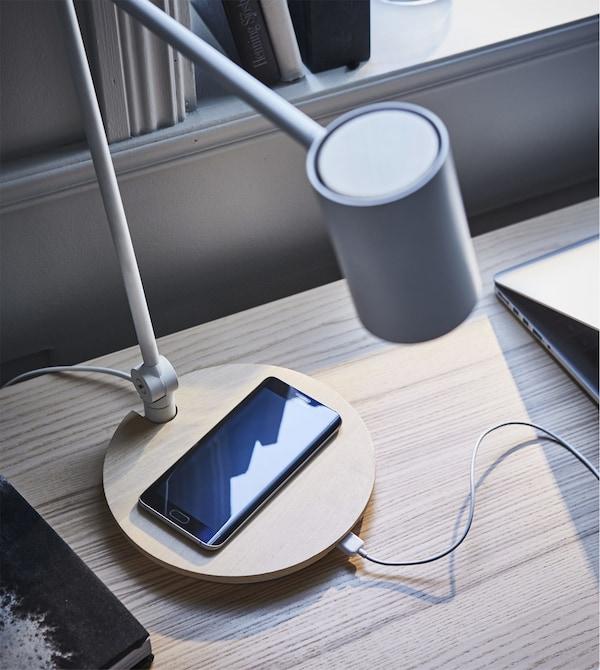 IKEA RIGGAD zuria eta grisa den aulki birakaria tapaki berdean biltzen erakusten duen GIF bat.