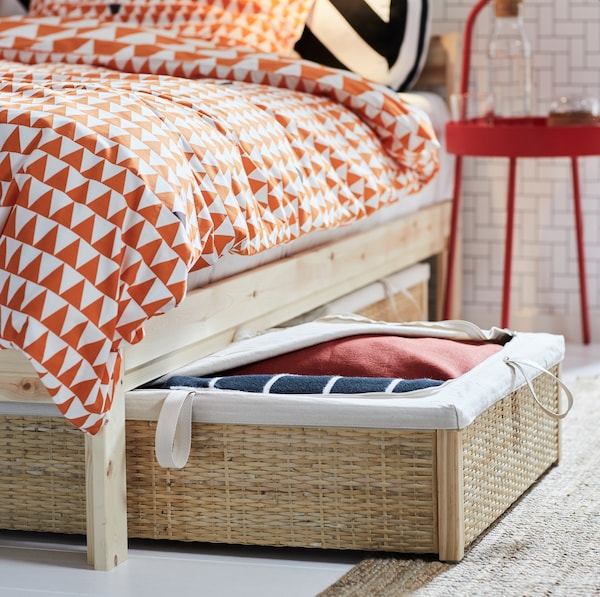 IKEA RÖMSKOG rattan bed storage box slides underneath bed frames as an extra clothes storage space.