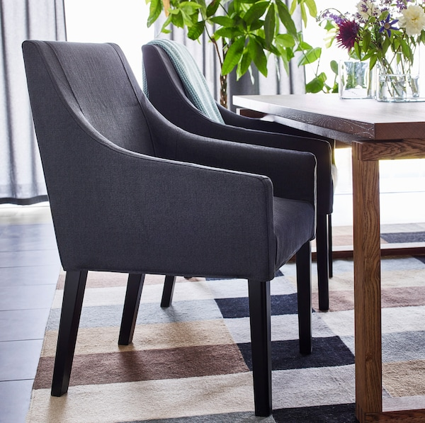 IKEA SAKARIAS dark grey dining chairs are designed with curved low armrests, and fit perfectly underneath MÖRBYLÅNGA oak veneer brown stained table.