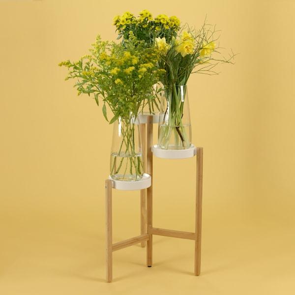 IKEA SATSUMAS Blumenständer mit drei großen Blumensträußen in Vasen darauf.
