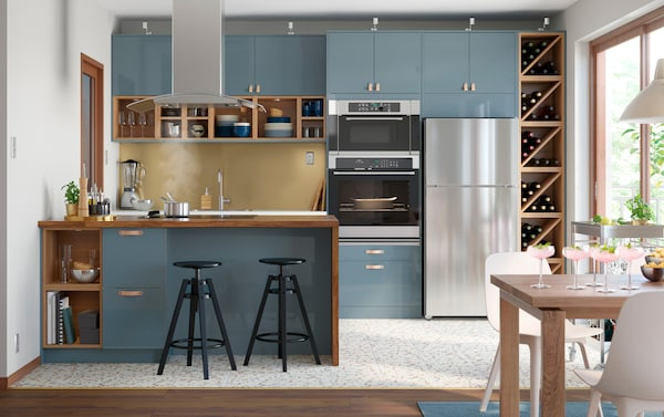 IKEA SEKTION series and VADHOLMA brown ash open storage wine shelves in a trendy kitchen with glossy blue kitchen cabinet door fronts with leather handles.