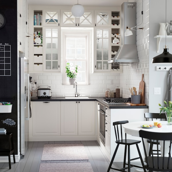 IKEA SEKTION white kitchen cabinets with vitrine glass doors surrounding a kitchen sink in a small kitchen area.