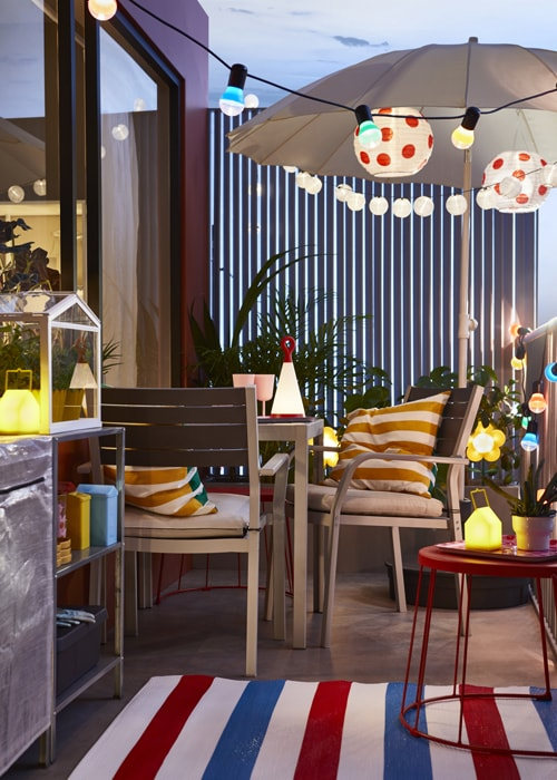 IKEA SJÄLLAND dark grey table and 2 chairs set sits on a small balcony with colourful outdoor decor and lighting.