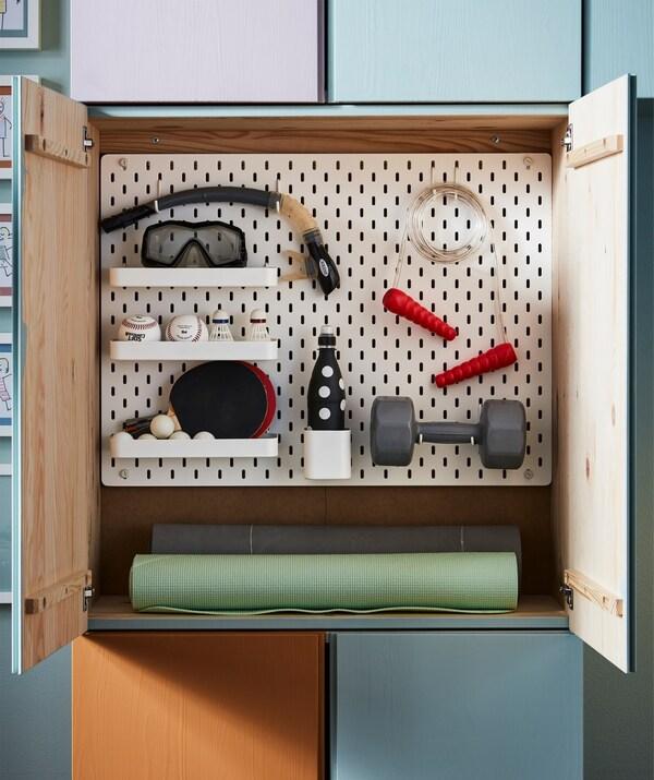 IKEA SKÅDIS ohol zulatuaren konbinazioa IVAR biltegiratze modulu batean, esekita dagoen kirol materialarekin.