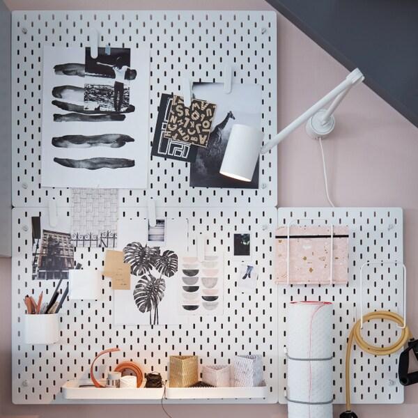 IKEA SKÅDIS Placar em branco numa parede rosa e azul, com papéis pendurados, canetas, e objectos de ginástica.