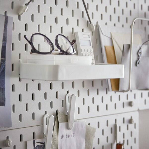 IKEA SKÅDIS Prateleira encaixada num placar com uns óculos pretos arrumados. Ao lado vê-se uma calculadora e alguns papéis arrumados.