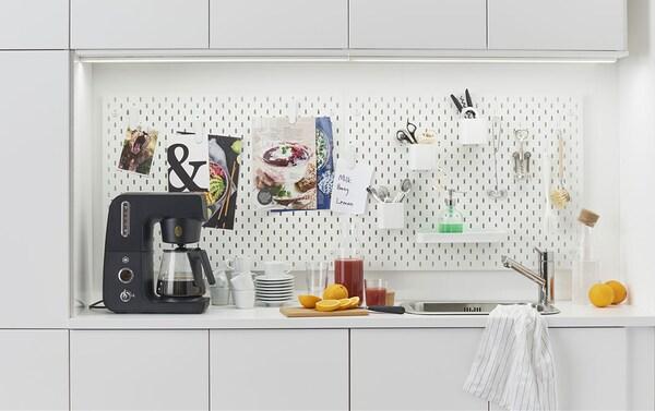 IKEA SKÅDIS säilytystaulun ansiosta toimiston keittiökin voi olla paikka, joka inspiroi ja kannustaa kommunikoimaan työkavereiden kanssa. Kuvassa myös valkoiset VEDDINGE keittiöovet sekä BOHOLMEN upotettava tiskiallas.