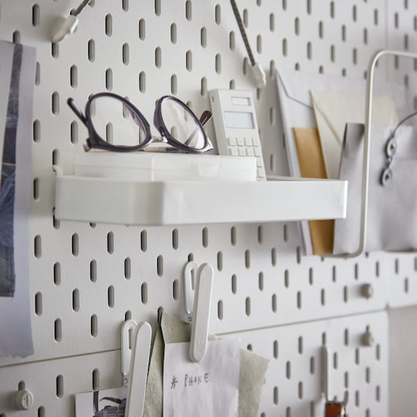 IKEA SKÅDIS shelf on a pegboard with some object's storage such as glasses. On the side there are a calculator and some storage papers.