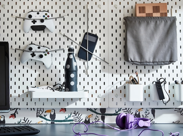 IKEA SKÅDIS white pegboard and add-on grey elastic cords holding game controllers and plug sockets.