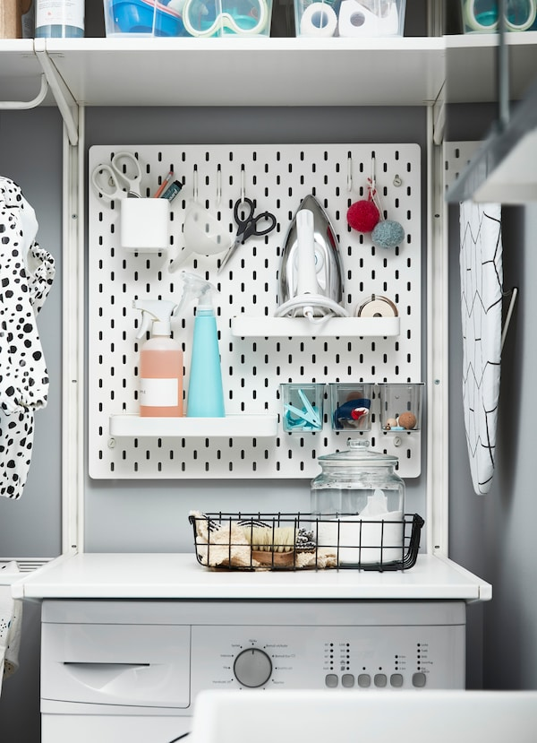 IKEA SKÅDIS white pegboard holding detergent and laundry supplies.