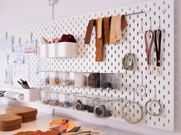 IKEA SKÅDIS white pegboard storing office supplies and accessories with optional coords, hooks and clear containers.