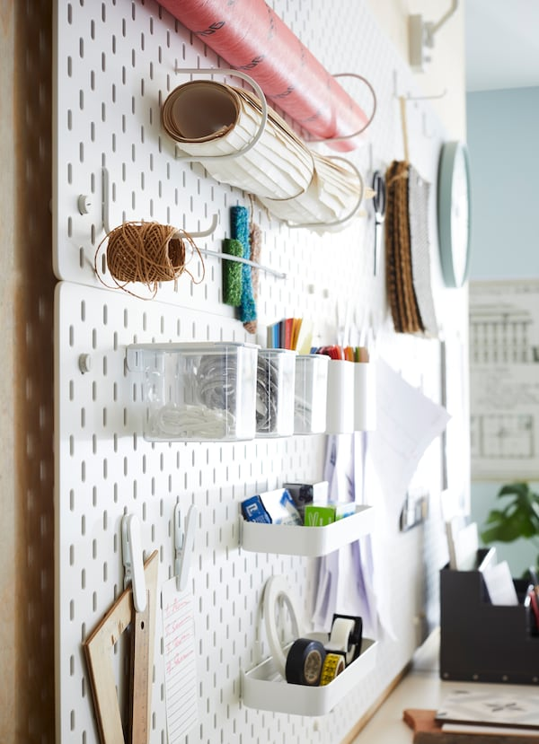IKEA SKÅDIS white pegboards holding office supplies in a communal area of the office.