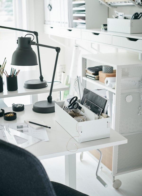 IKEA SKARSTA white sit and stand desk has a crank handle underneath the table to adjust and customise the height.