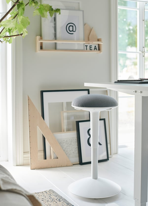 IKEA SKARSTA white sit and stand desk has a crank to adjust the worktop's height. NILSERIK stool with light grey cushion also adjusts for flexible seating.
