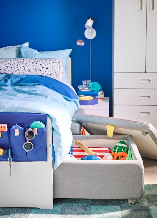 IKEA SLÄKT white bedframe and grey cushioned storage compartment, ajar to reveal sports equipment and toys.