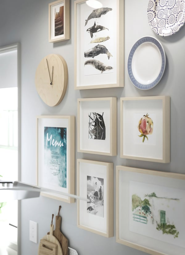 IKEA SNAJDARE birch plywood clock placed in a gallery wall.