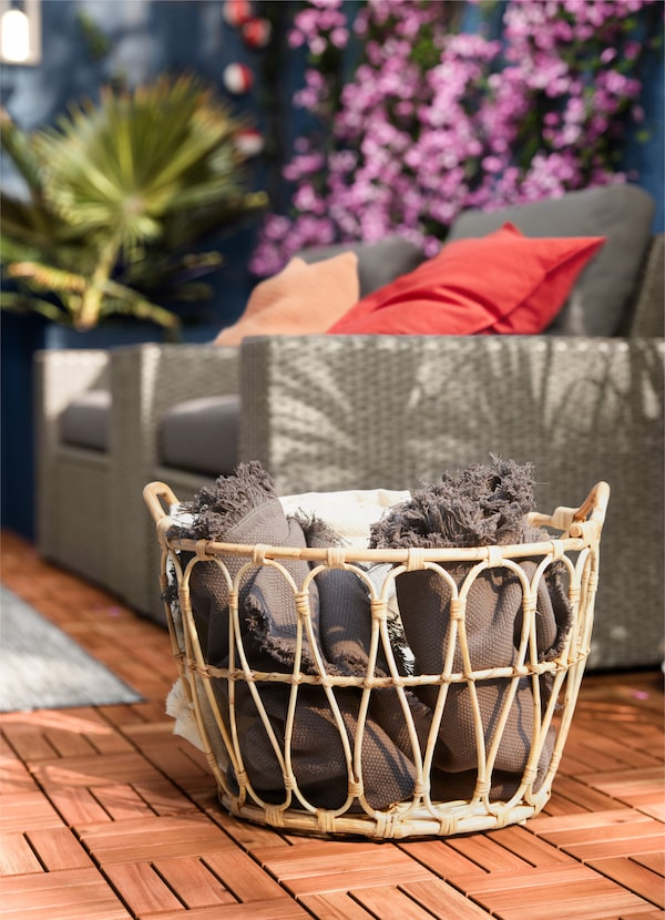 IKEA SNIDAD rattan basket holding textiles and blankets in an outdoor space.